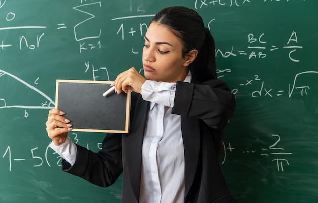 Pensando giovane insegnante femminile in piedi davanti alla lavagna tenendo mini lavagna con incagliato per bordo in classe in