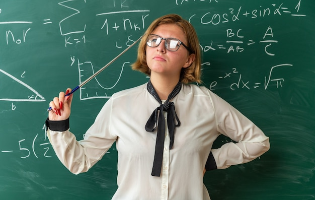 교실에서 엉덩이에 손을 대고 포인터 스틱을 들고 칠판 앞에 서있는 안경을 쓰고 생각하는 젊은 여성 교사