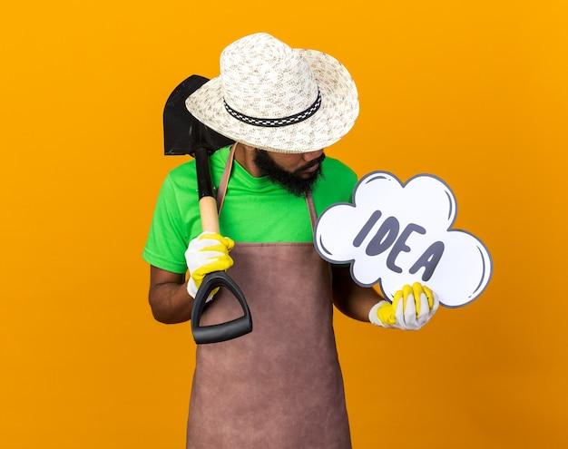 Pensando giovane giardiniere afro-americano che indossa cappello e guanti da giardinaggio tenendo la vanga e guardando la bolla dell'idea in mano isolata sul muro arancione