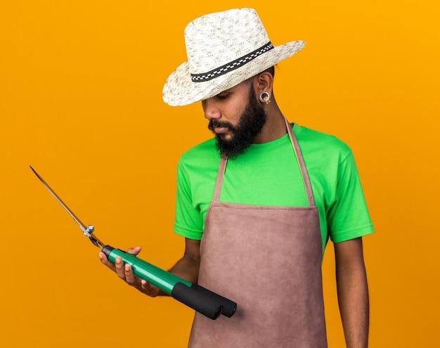ガーデニングの帽子をかぶってクリッパーズを見ている若い庭師のアフリカ系アメリカ人の男を考える