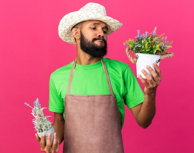 植木鉢の花を持って見ているガーデニングの帽子をかぶっている若い庭師のアフリカ系アメリカ人の男を考える