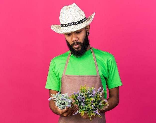 Pensando a un giovane giardiniere afroamericano che indossa un cappello da giardinaggio che tiene e guarda i fiori in un vaso di fiori