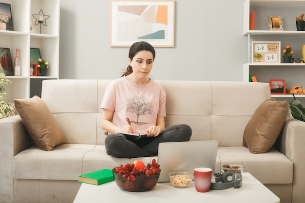 거실에서 노트북을 보고 있는 커피 테이블 뒤에 소파에 앉아 노트북을 들고 생각하는 어린 소녀