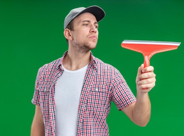 녹색 벽에 격리된 걸레 머리를 들고 모자를 쓰고 있는 젊은 남자 청소기