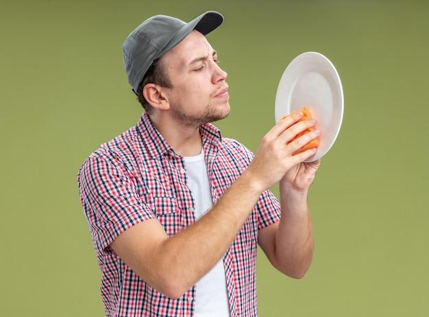 올리브 녹색 벽에 격리된 스폰지로 모자 세척 접시를 쓰고 있는 젊은 남자 청소기