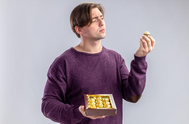 Думающий молодой парень в день святого валентина держит и смотрит на коробку конфет, изолированные на белом фоне
