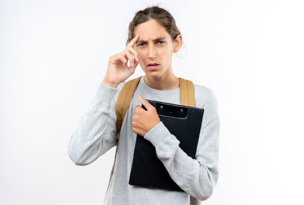 Pensando giovane studente che indossa uno zaino che tiene appunti mettendo il dito sulla fronte isolata sul muro bianco