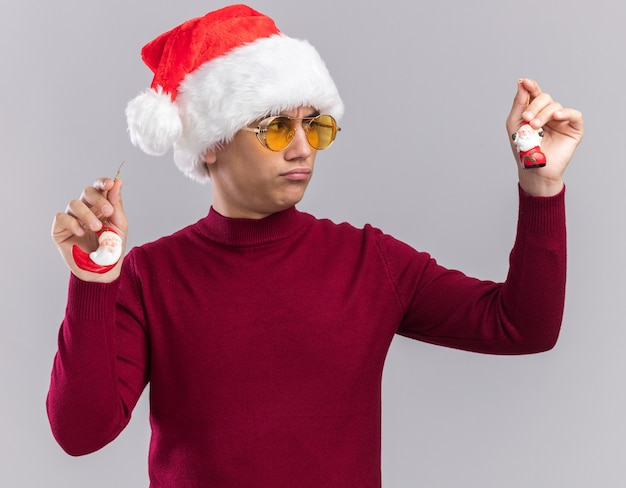 Thinking young guy wearing christmas hat holding and looking at christmas toys isolated on white wall