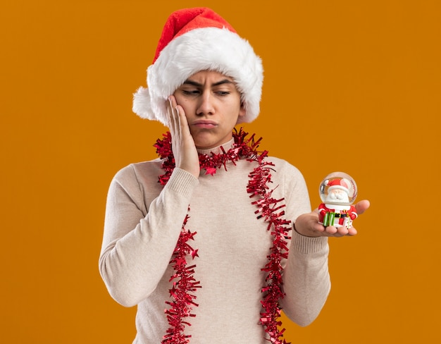 Thinking young guy wearing christmas hat with garland on neck holding and looking at christmas toy putting hand on cheek isolated on yellow wall