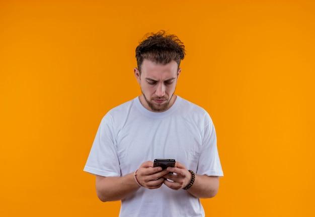 Думающий молодой парень в белой футболке, глядя на телефон в руке на изолированной оранжевой стене