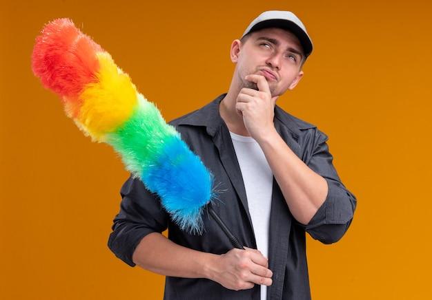 오렌지 벽에 고립 된 턱을 잡고 pipidaster를 들고 t- 셔츠와 모자를 쓰고 생각 젊은 잘 생긴 청소 남자