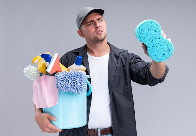 Thinking young handsome cleaning guy wearing t-shirt and cap holding bucket of cleaning tools and looking at sponge in his hand isolated on white wall