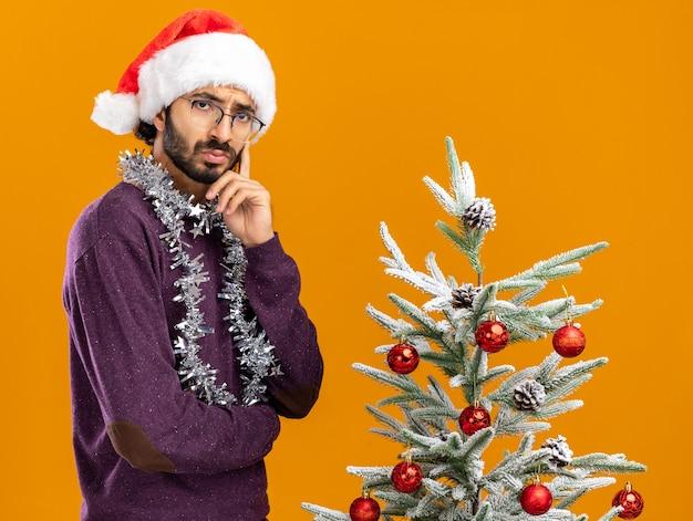 Pensando giovane bel ragazzo in piedi vicino albero di natale che indossa il cappello di natale con la ghirlanda sul collo mettendo il dito sulla guancia isolato su sfondo arancione
