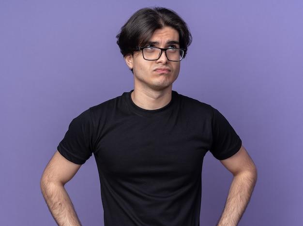 검은 티셔츠와 보라색 벽에 고립 된 안경을 쓰고 생각하는 젊은 잘 생긴 남자