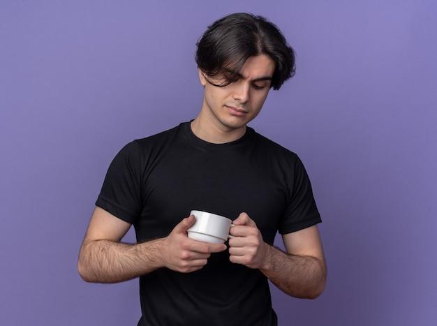 紫色の壁に隔離されたコーヒーのカップを保持し、見て黒いtシャツを着ている若いハンサムな男を考えて