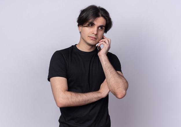 검은 티셔츠를 입고 생각 젊은 잘 생긴 남자가 흰 벽에 고립 된 전화에 말한다