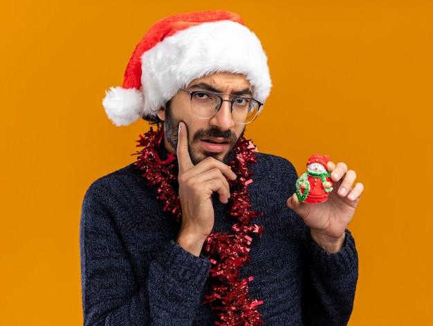 Pensando giovane bel ragazzo che indossa il cappello di natale con la ghirlanda sul collo tenendo il giocattolo mettendo il dito sulla guancia isolato su sfondo arancione