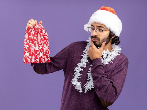 首に花輪とクリスマスの帽子をかぶって、青い背景で隔離のクリスマスバッグを見て若いハンサムな男を考えて