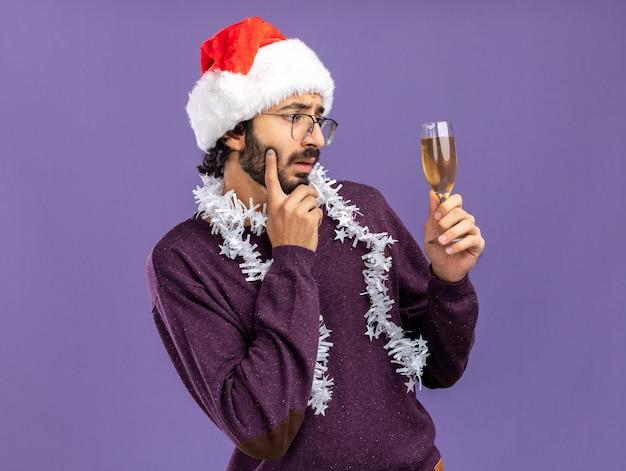 首に花輪とクリスマスの帽子をかぶって、青い背景で隔離の頬に指を置くシャンパンのガラスを見て若いハンサムな男を考えて
