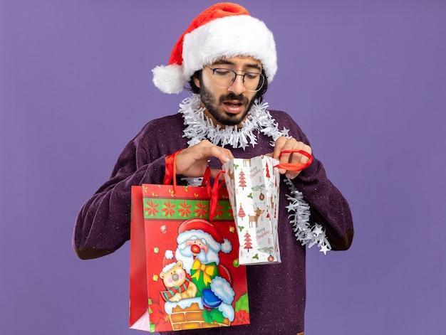 首に花輪とクリスマスの帽子をかぶって、青い背景で隔離のギフトバッグを見て若いハンサムな男を考えて