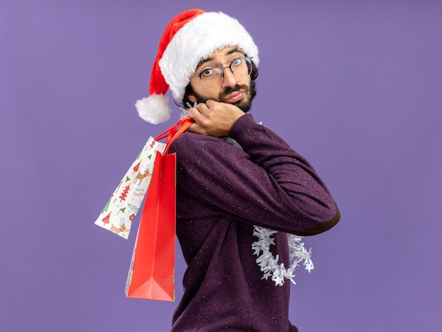 青い背景で隔離の肩にギフトバッグを保持している首に花輪とクリスマスの帽子をかぶって若いハンサムな男を考えて