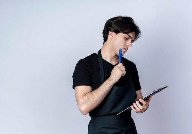 制服を着た若いハンサムな男性の理髪師を考えてクリップボードを持って見て、白のあごにペンを置く