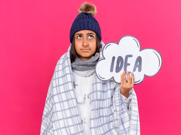 분홍색 배경에 고립 된 아이디어 거품을 들고 격자 무늬에 싸여 스카프와 겨울 모자를 쓰고 찾고 생각 젊은 아픈 여자