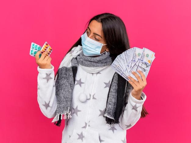 Pensando giovane ragazza malata che indossa la maschera medica con sciarpa tenendo i soldi e guardando le pillole in mano isolato su sfondo rosa