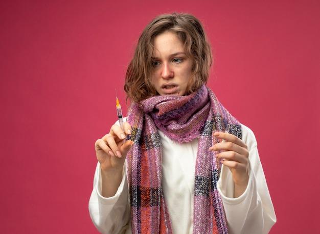アンプルを保持し、ピンクの壁に隔離された彼女の手で注射器を見て白いローブとスカーフを身に着けている若い病気の女の子を考えて
