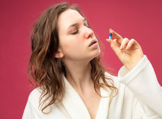 Думающая молодая больная девушка в белом халате держит и смотрит на таблетку, изолированную на розовой стене