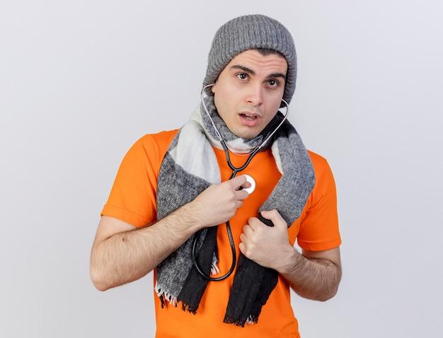 Pensando giovane uomo malato che indossa il cappello invernale con sciarpa che indossa e ascolta il proprio battito cardiaco con lo stetoscopio isolato su sfondo bianco