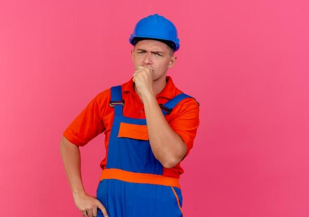 ピンクのあごに拳を置く制服と安全ヘルメットを身に着けている若い男性ビルダーを考える