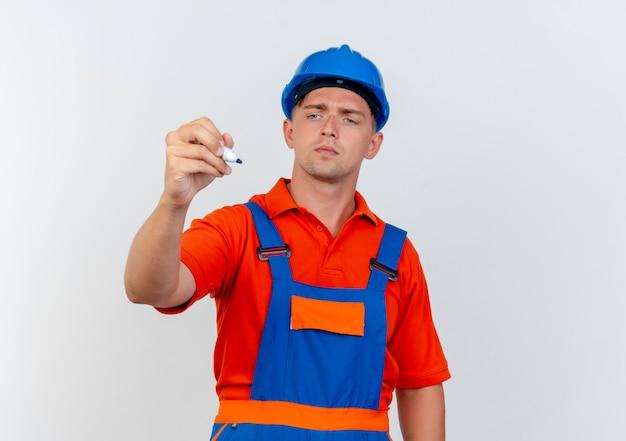 Pensando giovane costruttore maschio che indossa l'uniforme e la tenuta del casco di sicurezza e guardando il pennarello su bianco