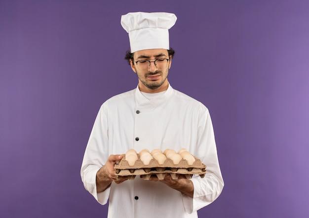 Pensando giovane cuoco maschio che indossa l'uniforme del cuoco unico e vetri che tengono e che esaminano lotto di uova sulla porpora