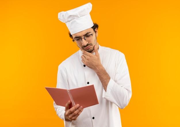 Pensando giovane cuoco maschio che indossa l'uniforme dello chef e bicchieri tenendo e guardando il taccuino e mettendo la mano sul mento isolato sulla parete gialla