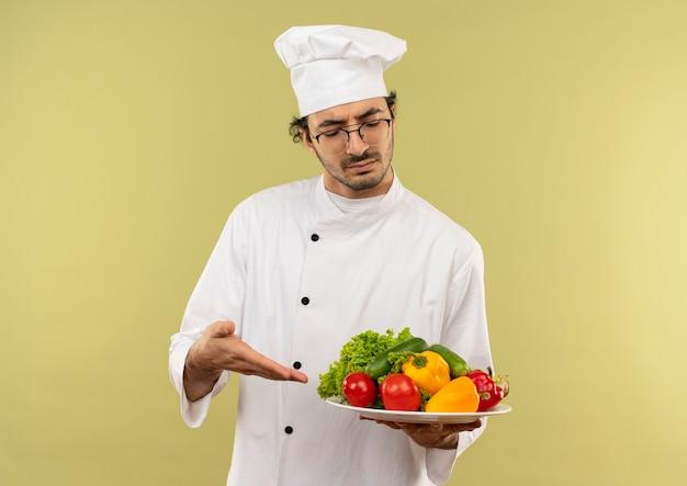 Pensando giovane cuoco maschio che indossa l'uniforme del cuoco unico e occhiali che tengono e punti con le verdure a mano sul piatto isolato sulla parete verde