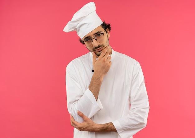 Pensare giovane maschio cuoco che indossa la divisa da chef e bicchieri mettendo la mano sul mento