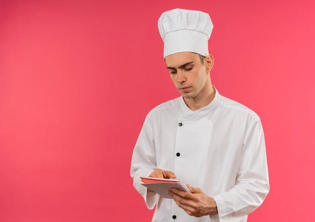 コピースペースのあるノートブックを持って見ているシェフの制服を着た若い男性料理人を考える