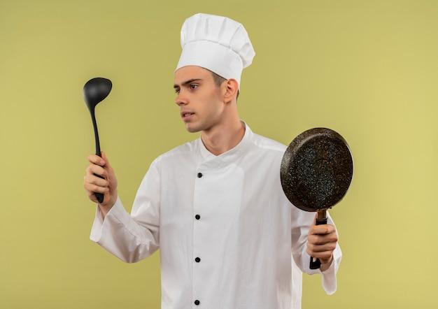 彼の手で取鍋を見てフライパンを保持しているシェフの制服を着ている若い男性料理人を考える