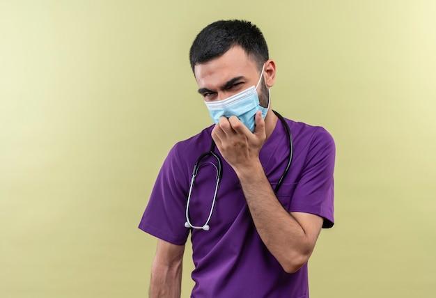 紫色の外科医の服と聴診器の医療マスクを身に着けている若い男性医師が孤立した緑の壁のあごに手を置いたと考えています
