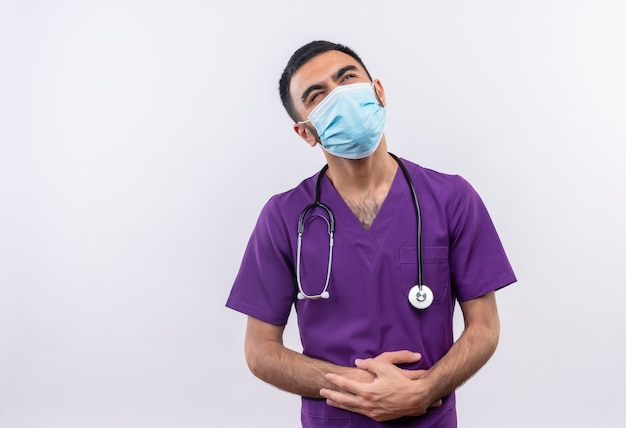 Thinking young male doctor wearing purple surgeon clothing and stethoscope medical mask put his hands on stomach on isolated white