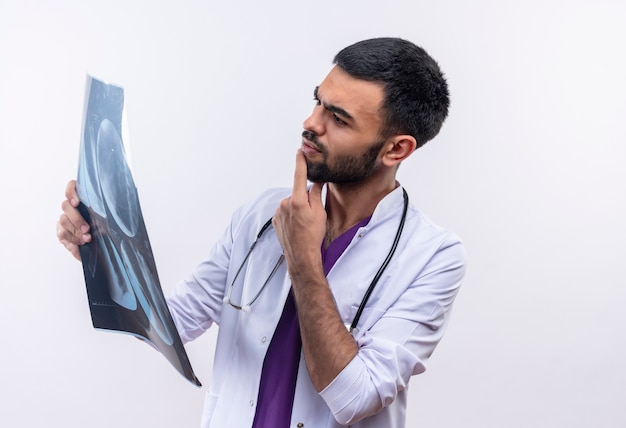 Думающий молодой мужчина-врач в медицинском халате со стетоскопом, глядя на рентгеновский снимок на руке на изолированном белом