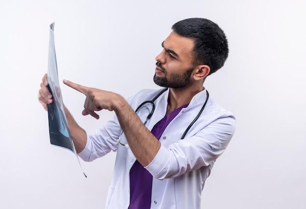 Думающий молодой мужчина-врач в медицинском халате со стетоскопом указывает на рентгеновский снимок в руке на изолированном белом