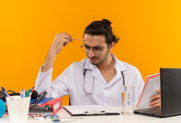 책상에 앉아 청진기와 의료 가운을 입고 의료 안경 생각 젊은 남성 의사