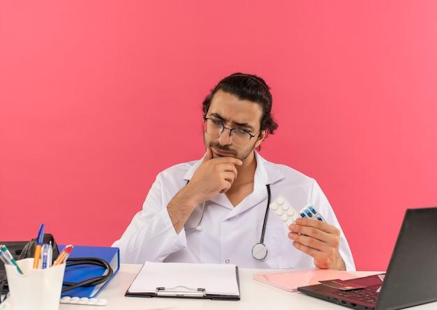 机に座っている聴診器で医療用ローブを着た医療用眼鏡をかけた若い男性医師を考える