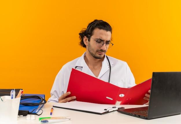 Pensando giovane medico maschio con occhiali medici che indossano accappatoio medico con stetoscopio seduto alla scrivania Foto Gratuite