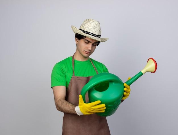 じょうろを持って見ているガーデニングの帽子と手袋を身に着けている制服を着た若い男性の庭師を考える