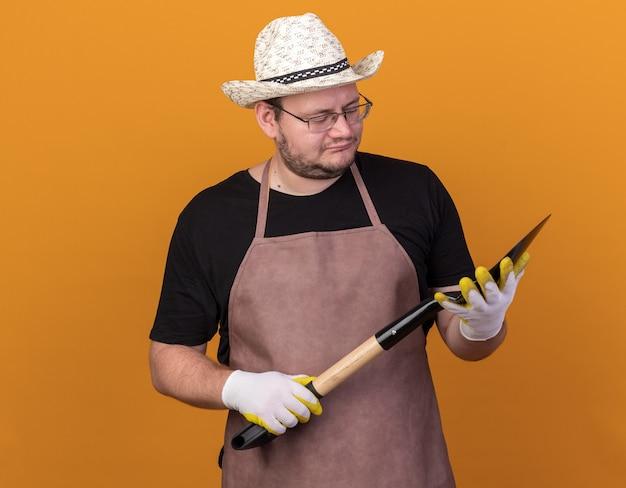 Pensando giovane giardiniere maschio indossando guanti e cappello da giardinaggio tenendo e guardando vanga isolato sulla parete arancione