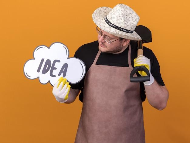 Pensando giovane giardiniere maschio che indossa guanti e cappello da giardinaggio tenendo la vanga e guardando la bolla di idea nella sua mano isolata sulla parete arancione