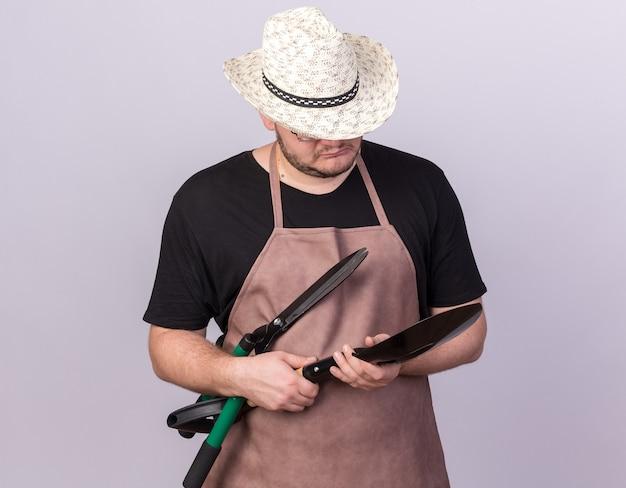 Думающий молодой мужчина-садовник в садовой шляпе держит и смотрит на лопату с кусачками, изолированными на белой стене